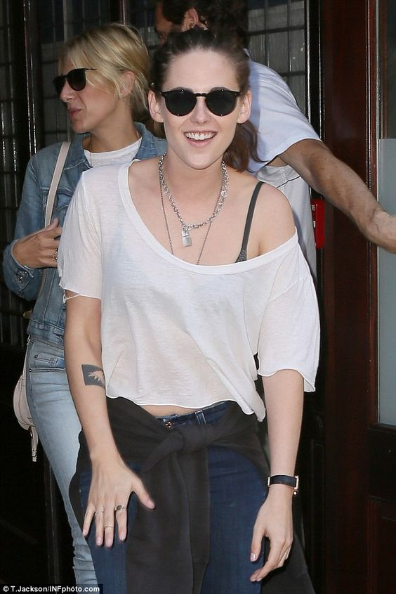 Upbeat: Kristen Stewart flashed a rare smile as she left her hotel and headed to dinner in...