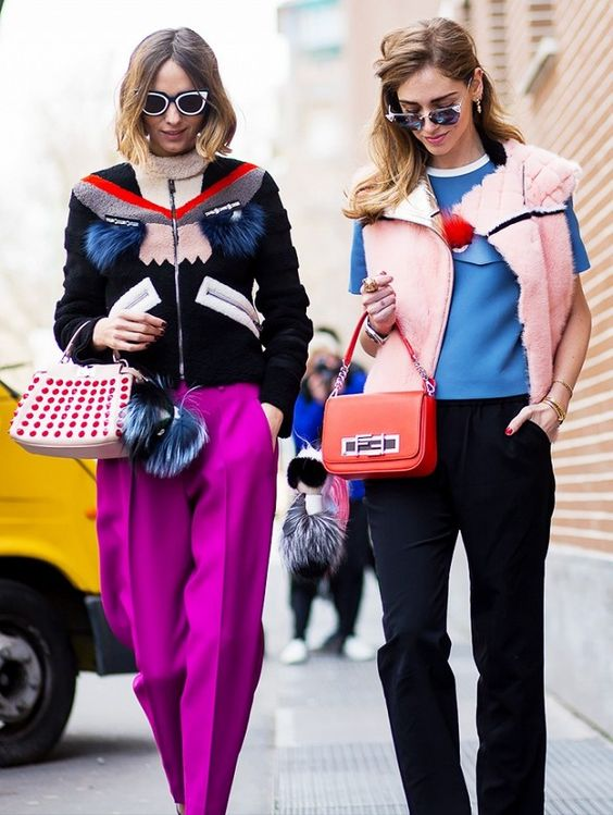 Left, Candela Novembre wears a Fendi zip-up jacket, fuchsia trousers, cat-eye sunglasses, and a studded Fendi bag. Right, Chiara Ferragni wears a Fendi vest, top, top-handle flap bag, and cat-eye sunglasses.