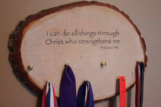 Ethan's sports and academic medal holder. Thrift shore wood slice, screw in hooks, and Philippians 4:13