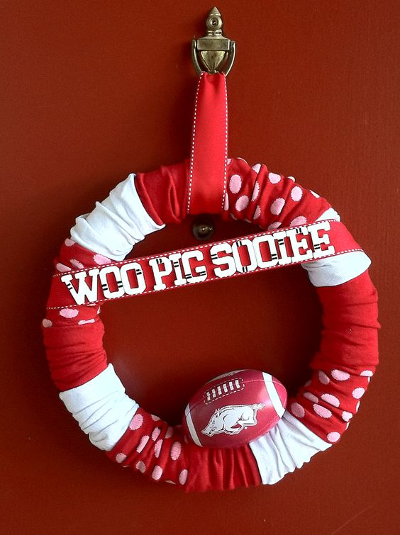 Razorback Sock wreath. These socks came from 2-3pks. from the Dollar Tree. Cut the toe off of each & carefully cut an opening in a foam wreath. Carefully slide each socks on, hiding the heels on the back of wreath & in the scruntches. Then decorate with whatever extras you desire! The football, ribbon, & painted wooden letters are just hot glued onto this wreath.