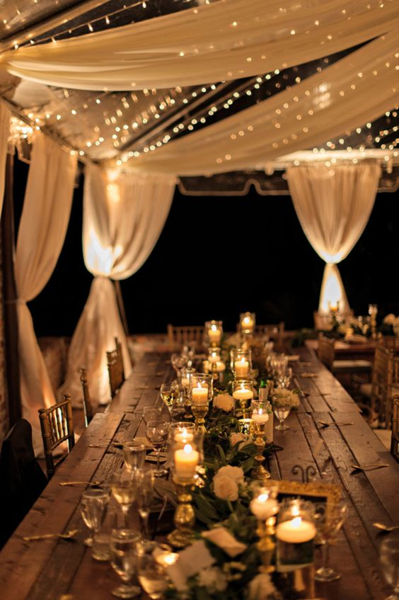 A combination of fabric and twinkle lights make for a beautiful layered look in a wedding tent!: