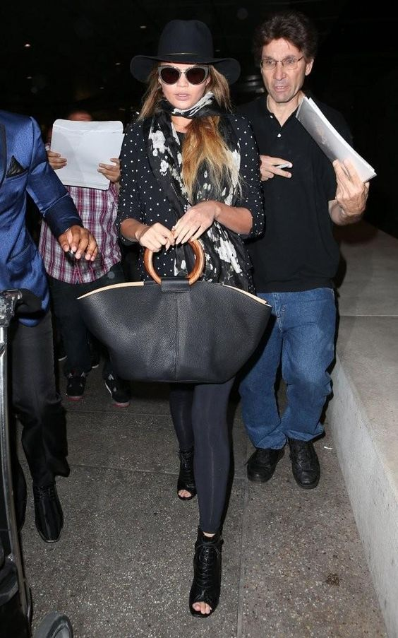 Chrissy Teigen wearing Janessa Leone Stephen Fedora, the Row Market Bag, Givenchy Floral Scarf, Saint Laurent Lace-Up Booties and Balenciaga Ba0033 57mm Cat Eye Sunglasses