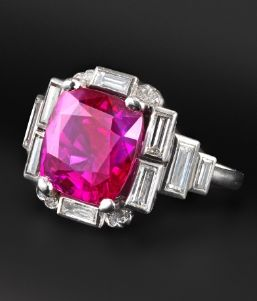 An Art Deco ruby and diamond ring, the cushion-shaped ruby weighs 6.17 carats and is set in platinum and white gold with ten baguette-shaped diamonds and eight small circular cut diamonds.