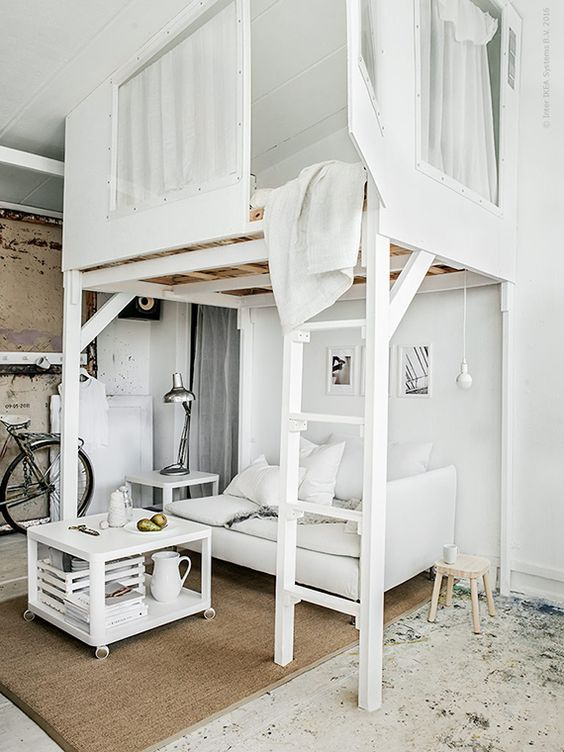 A white loft bed with a beautiful latter.