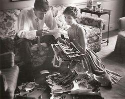 1954. Mai. Jack and Jackie browsing through a newly unpacked box of wedding photos. Photograph by Orlando Suero