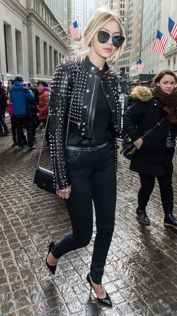 Gigi Hadid at New York Fashion Week wearing a studded leather jacket, mirrored sunglasses, jeans, and pointed heels: