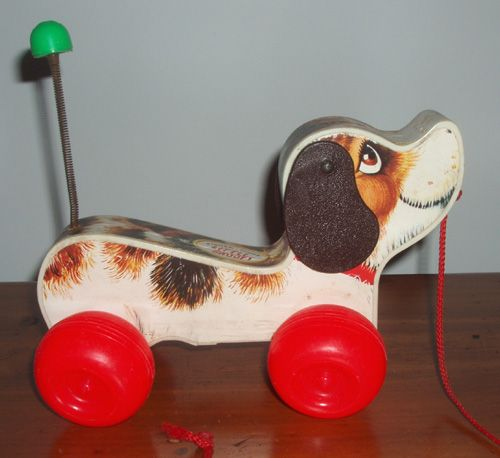1965 Fisher Price pull toy featuring that crazy dog from the Peanuts comic strips by Charles Schultz.  Has a wooden body with colorful graphics, floppy brown ears that move, and bright red wheels that make clacking noise and wooble when it's pulled. Spring spiral tail with green tip for that final added flair