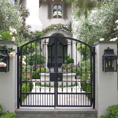 Garden gate ideas and inspiration: Dark iron formal gates flanked by lanterns open to a European style courtyard and magnificent house. #gardengate #courtyard #Frenchcountry #irongate