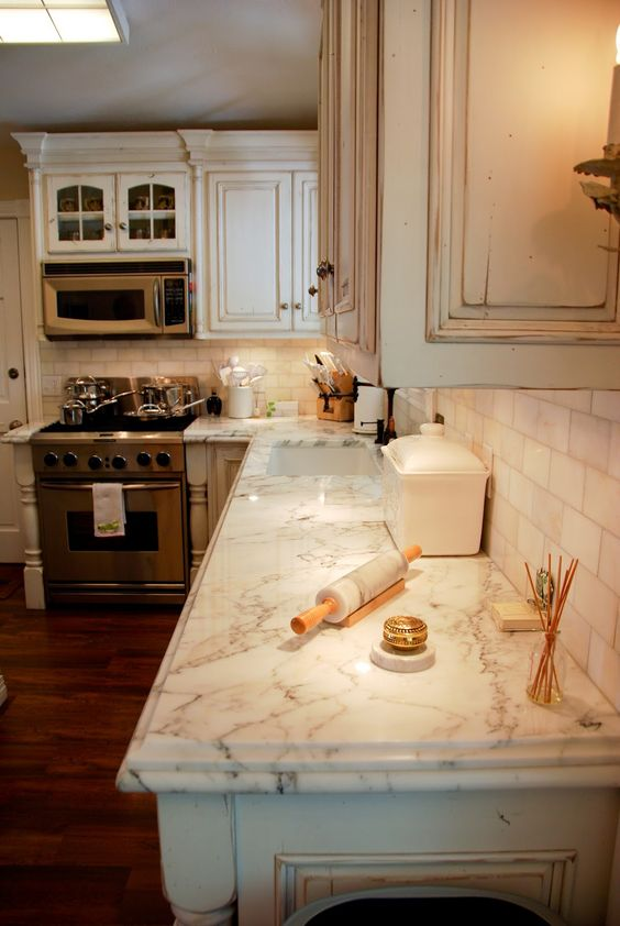 Here you get a stylish look to the calcatta gold because it has a unique edge on the countertop. It also creates a unique and elegant accent to go with the rustic cupboards.