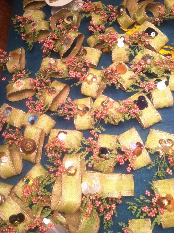 70 napkins rings with burlap and gold ribbon, vintage buttons, and little bit of green and pink for the bride.