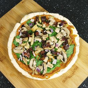 Autoimmune Protocol (AIP)-friendly Pizza topped with spinach, onion, roasted chicken and bacon