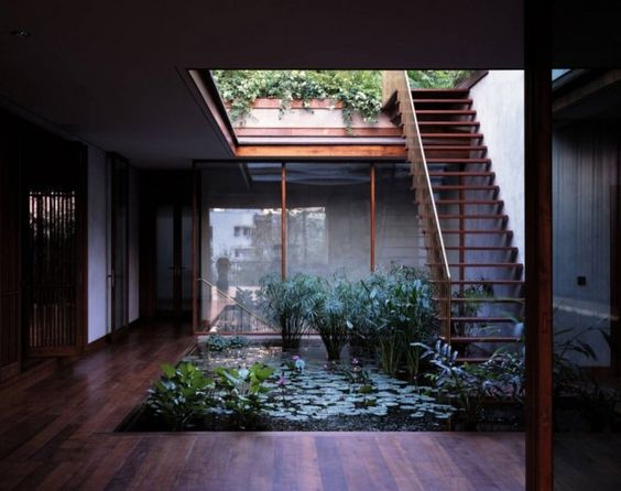A central courtyard harbors a still lily pad pool that reflects the sky, and the rise of a wooden staircase that appears to float on the surface of the water.