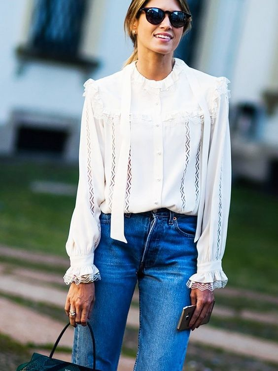 A fancy ruffle-trimmed blouse is worn with high-waisted jeans, a satchel, and round sunglasses