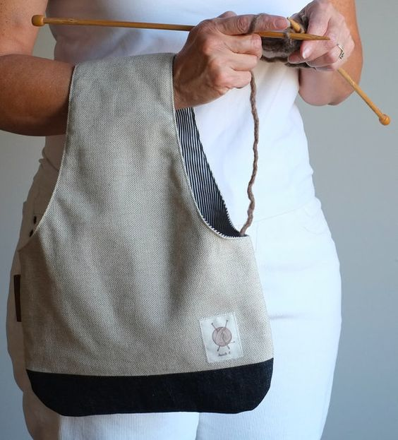 """Yarn Bag Knitting Bag Knitter's gift Linen Wristlet by OtterburnPQ This wristlet is the big version, it mesures 15"""" X 11"""". It can handle multiple yarn balls or big skeins. It is made of beige linen and the interior is dark blue and white stripes.  It has a big leather tag on the side. The bag is reversible! It looks good inside out!"""