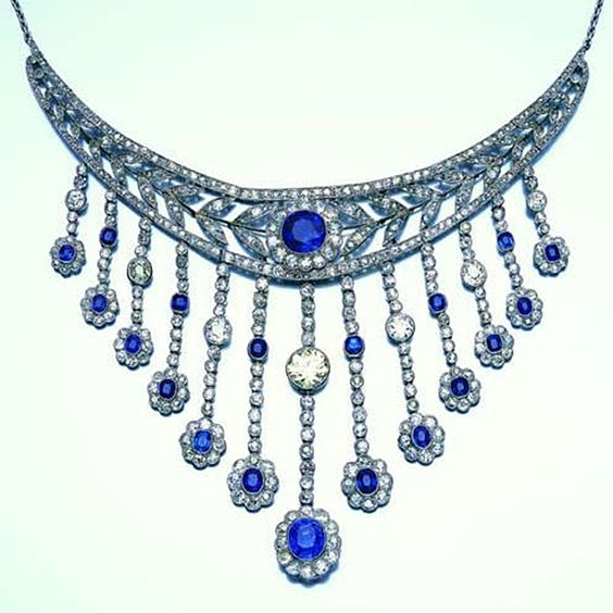 A belle époque sapphire and diamond fringe necklace,  the curving openwork plaque designed as a garland with a sapphire and diamond floral cluster at the centre, supporting a graduating fringe of articulated drops each with a sapphire and diamond floral termination, millegrain-set throughout with circular and mixed-cut sapphires and old brilliant, single and rose-cut diamonds, diamonds approximately 19.00 carats total