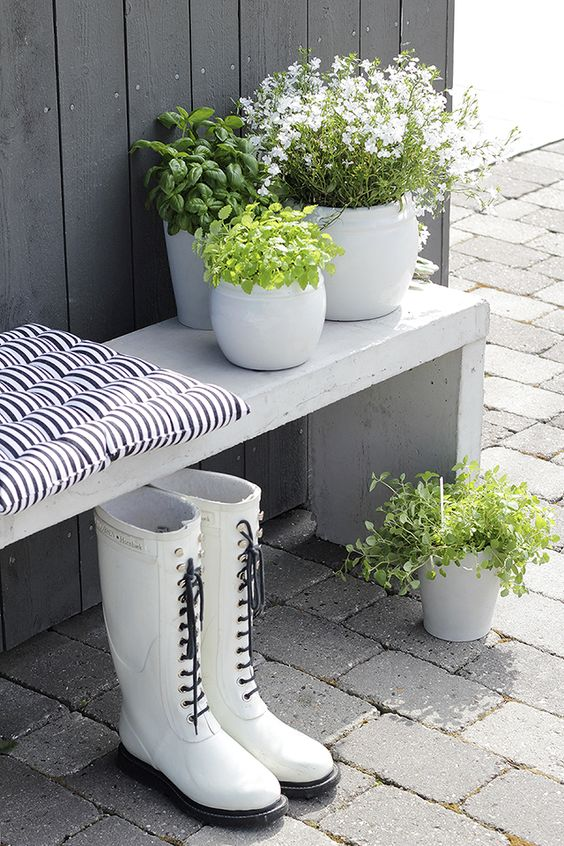 White wooden bench against dark grey wall; pots: