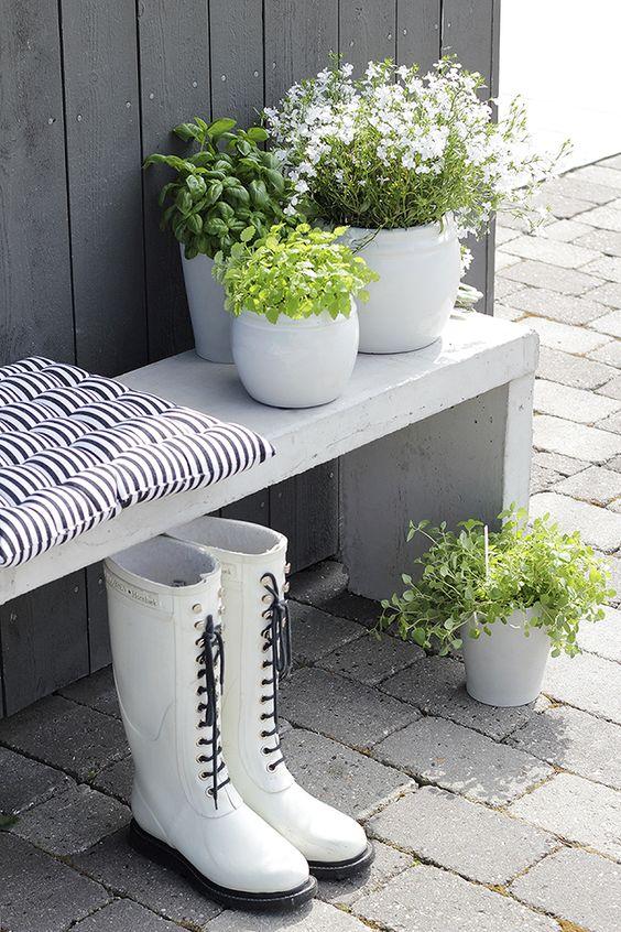 White wooden bench against dark grey wall; pots: