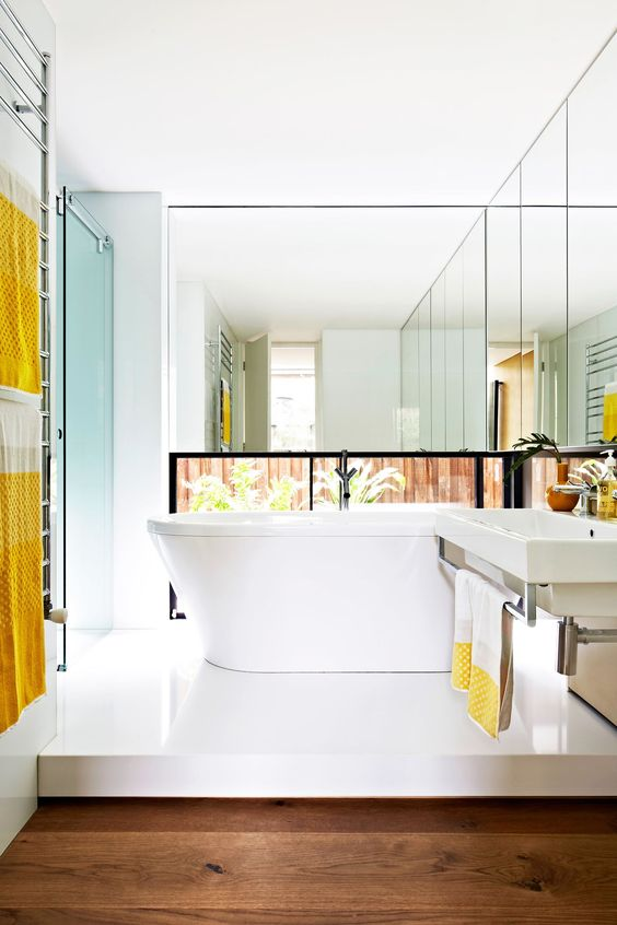 """Wrap around mirrored panels make the compact main bathroom feel larger; the low-set window allows natural light to flood in without compromising privacy.   **Bath** and **basin** from [Rogerseller](http://www.rogerseller.com.au/