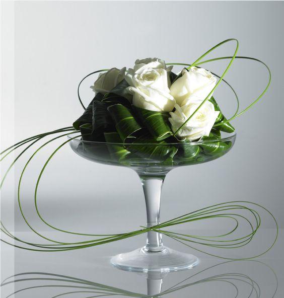 Bear grass, roses and aspidistra leaves elegantly arranged on pedestal dish.
