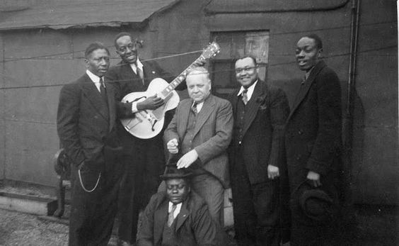 Lester Melrose with some of his blues artists pictured around 1940. From left: Ernest 'Little Son Joe' Lawlars, Big Bill Broonzy, Lester Melrose, Roosevelt Sykes, St. Louis Jimmy Oden. Front: Washboard Sam.