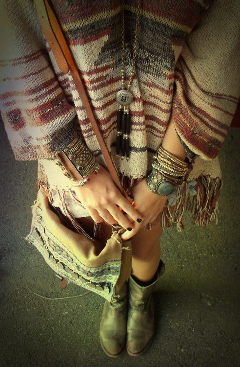 ethnic textile with fringe, shorts, scuffed leather booties, silver/turquoise navajo wrist piles and long necklace.
