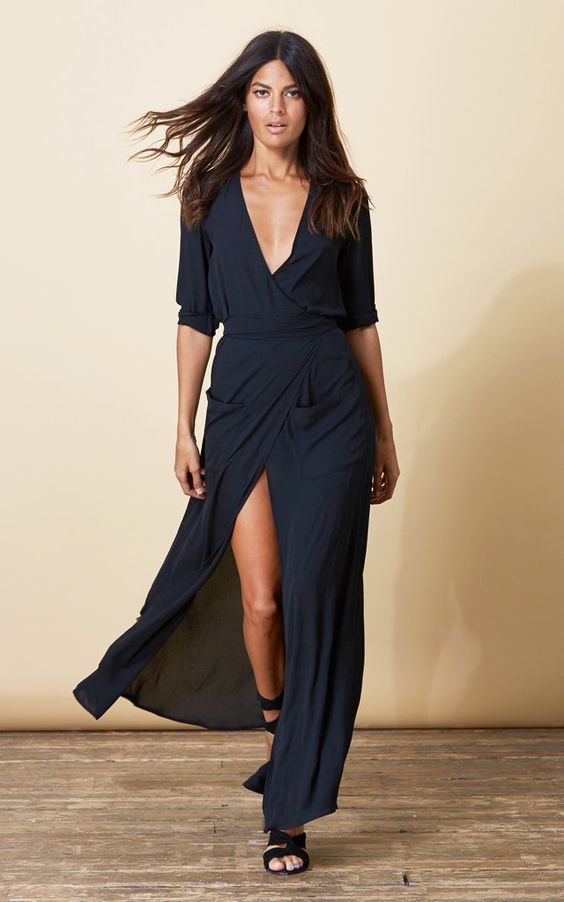 Long black maxi wrap dress in a lovely, flowing fabric. Full skirt with a high front slit, tie belt and deep pockets. Shop now.