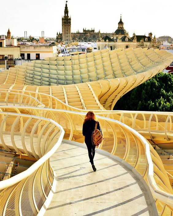 A woman on the roof of Metropol Parasol with La Giralda and the Cathedral in…