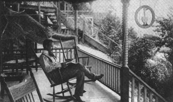 L. Frank Baum reading on the porch with hammock.: