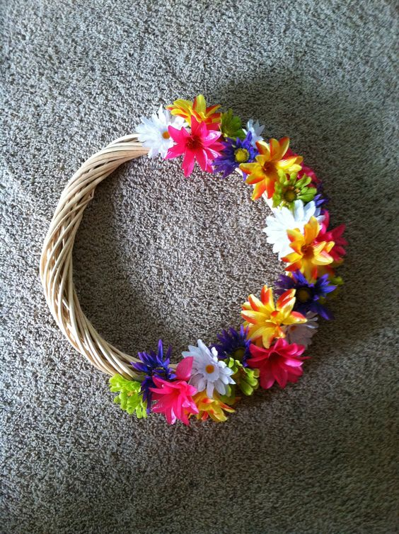 Wood wreath from the thrift store and dollar store fake flowers. Just hot glue them on! Very summery!