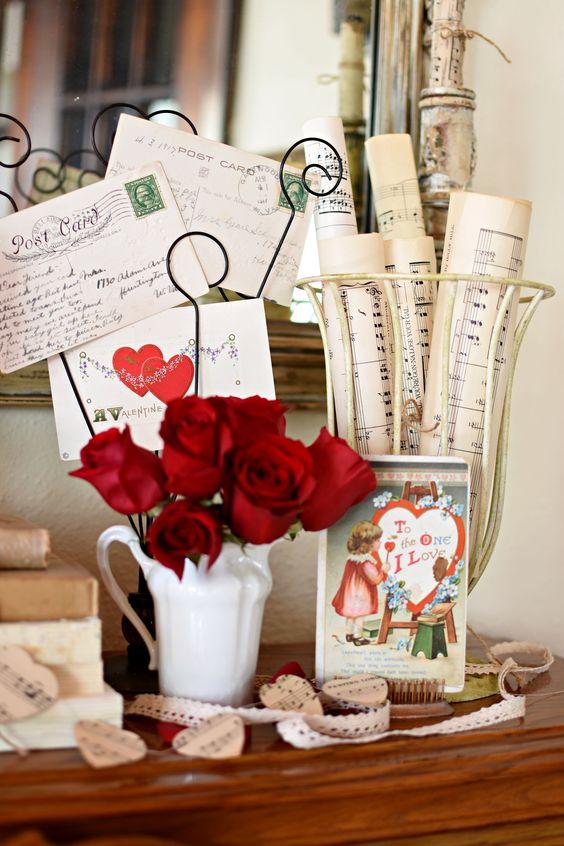 Romantic Valentine vignette with red roses, vintage sheet music rolls and vintage Valentine postcards