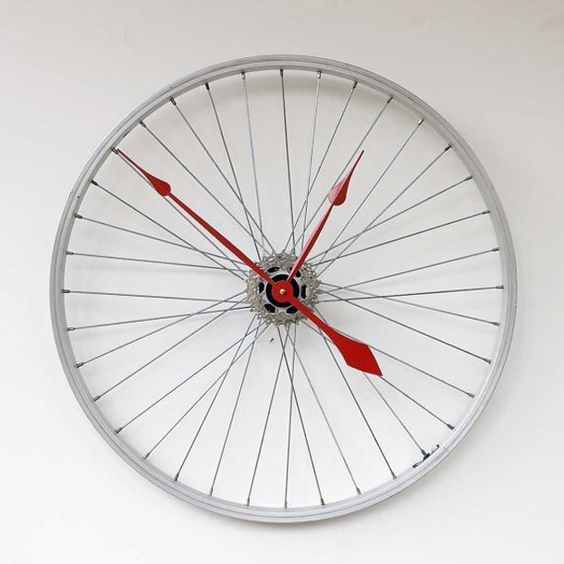 This clock was made from a recycled aluminum Mongoose bike wheel. The wheel mounts directly to the wall through the hub using a hollow wall anchor and gives the illusion that it is floating off the wall. The clock movement is a high torque German quartz movement and is attached to a set of rear cassette gears to conceal the movement. (Designed by pixelthis)
