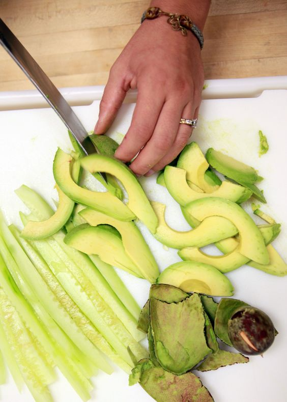 Slicing the avocado for handmade California sushi  roll