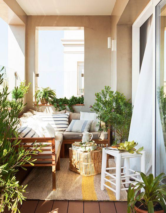 Terraza pequeña cubierta con sofá rinconero, mesa de centro de caña, taburete de madera y cojines vintage a rayas