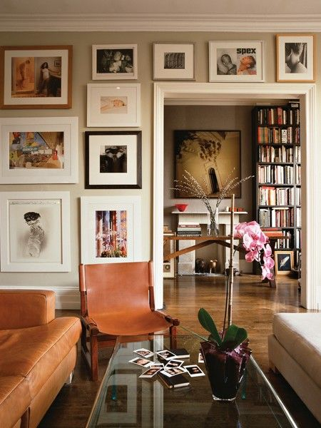 Framed art in varying sizes lends a casual feel. Use every available inch of wall space by hanging artwork from baseboard to crown moulding and around a doorway. This collection is varied in subject matter, size and framing, but it looks cohesive thanks to a colour palette — warm neutrals punctuated with black and white — reflected in the rest of the room. Photos by Chris Tubbs. Source: House & Home Best Decorating 2012 Special Issue: