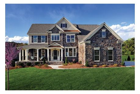 A rich stone exterior with a wrap-around front porch defined by graceful columns. The Ashville Model from Drees Homes. Churton Grove Community, near Raleigh, NC.
