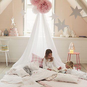 Une ambiance de princesse avec des murs rose pastel et des coussins sous un baldaquin dans une chambre de petite fille #enfants