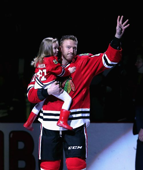 Marian Hossa of the Chicago Blackhawks holding daughter Mia acknowledges the crowd at a ceremony honoring his 1000 point before a game against the...