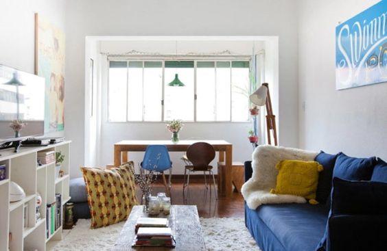 A decoração, neutra e masculina, se baseia na combinação de amarelo, nas almofadas, azul, no sofá e cadeira, marrom, no piso e mobiliário, e branco. Uma graça.
