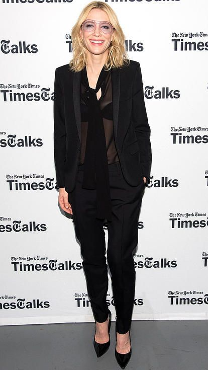 Cate Blanchett in a black tuxedo, sheer bow top, and quirky pink glasses