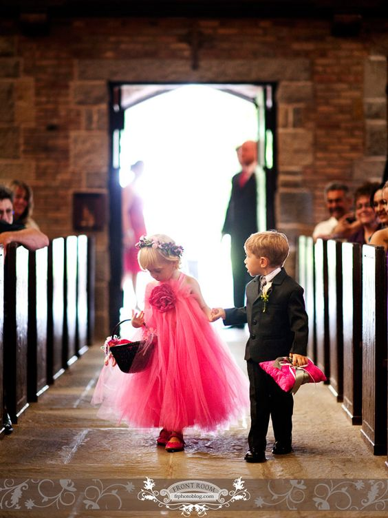 A cute pink tutu dressed flower girl and ring bearer holding a pink pillow. Photo by: FRPhoto