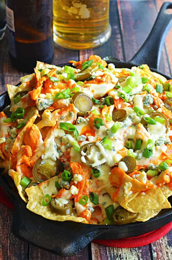 Loaded Buffalo Chicken Nachos - Shredded buffalo chicken, cheesy ranch queso, blue cheese crumbles, pickled jalapenos, & chopped green onions
