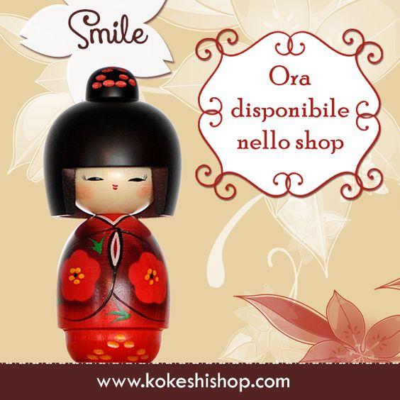 Estremamente femminile, Smile è una bambola Kokeshi dal viso chiaro e le guance rosee, con un kimono rosso vivo decorato con fiori selvatici e fili d'erba e con un ornamento sui capelli.