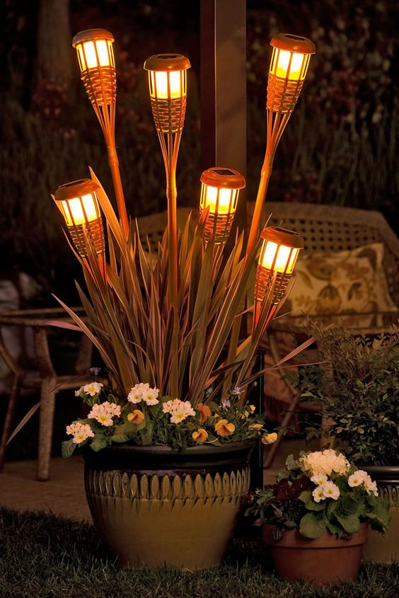 Create a planter with tiki torch lights for a glowing evening!  We can help you create this look at Old Time Pottery!