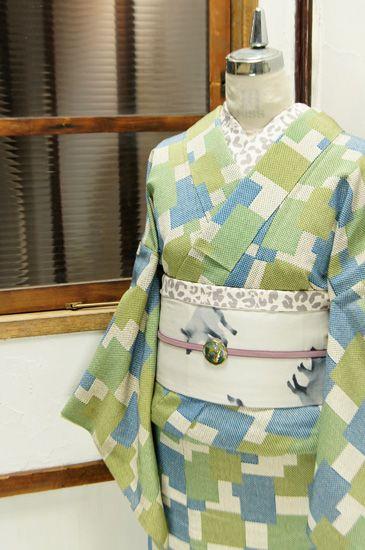 空色と若葉色の階調美しく染め出されたウッドパズルのようなモダンパターンが遊び心をさそう袷着物です。