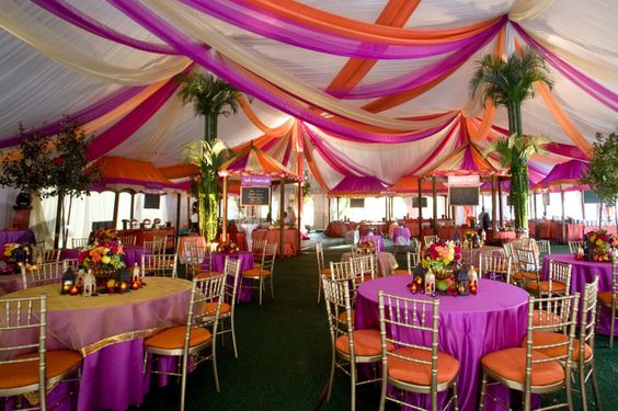 Here's a fun idea... bring the inside outside (with a tent) then pull it back inside (with the intricately decorated tables and chairs) and then take it back outside (with the palm trees and fabric-draped, palapa-like ceiling treatments). Tricky AND tricked-out!