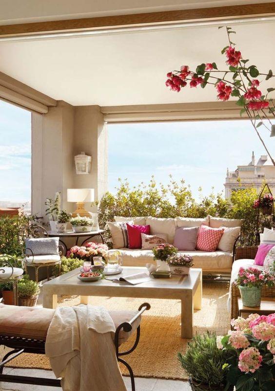 un canapé avec des coussins et une table basse en bois sur la terrasse: