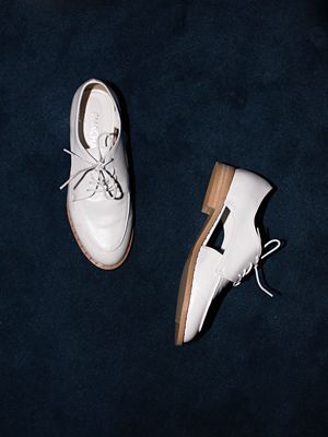 white cut-out flat shoes
