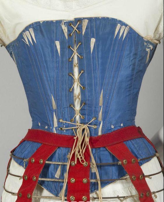 1860s blue silk corset. Steel bones and busk, brass hardware, cream cotton…: