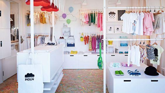 Loja de roupa de criança decorada com soluções de arrumação com gavetas, prateleiras e varões