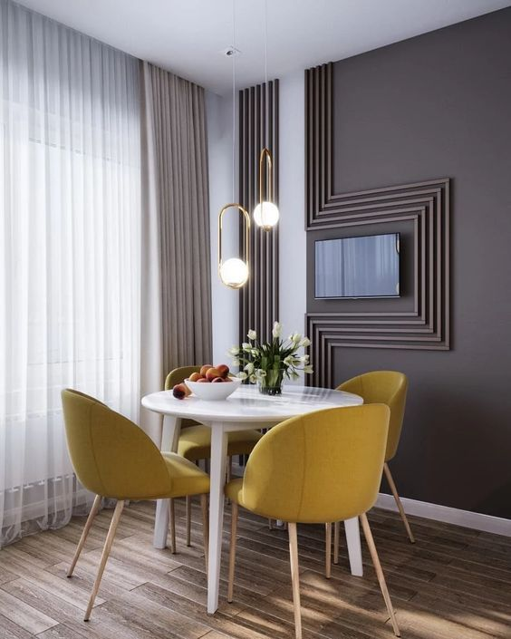 There is nothing more satisfactory than enjoying breakfast in a cozy nice breakfast nook. The shades of grey, wooden floors, small round white table, amazing yellow dining chairs, and our lovely modern golden pendant lights, makes this characteristic look a dream come true. The white curtains make the perfect match with the dining table, and the entire space makes you feel welcomed. Don't hesitate on placing lighting pieces in small spaces, they make the entire difference!